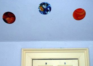 Michael's children drew the pictures of planets on the slant over their beds